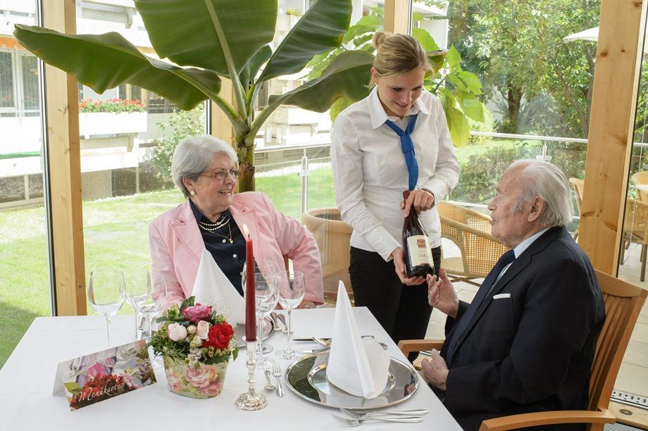 Paar und Servicekraft im Café-Restaurant eines KWA Wohnstifts