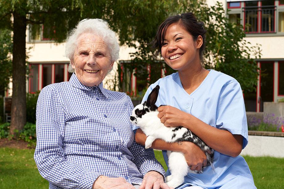 Bewohnerin und Pflegerin des KWA Luise-Kiesselbach-Hauses mit Kaninchen