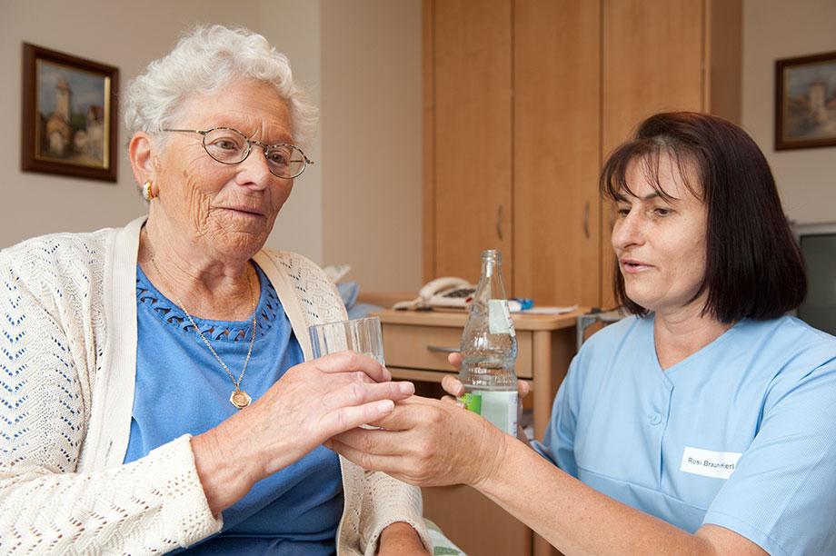 Pflege im KWA Luise-Kiesselbach-Haus: Pflegerin gibt Bewohnerin ein Glas Wasser