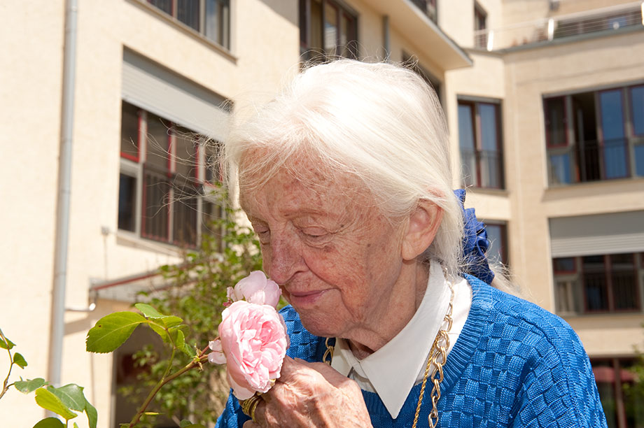 Bewohnerin des KWA Luise-Kiesselbach-Hauses mit Rose
