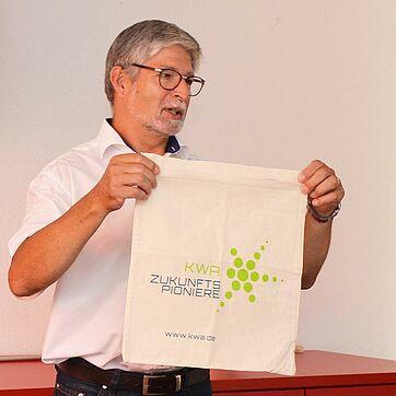 Stiftsdirektor Herbert Schlecht präsentierte die erste Stofftasche mit dem Logo der KWA Zukunftspioniere; Spenden für die Tasche kommen Projekten der engagierten Bewohner zugute