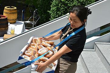 Mitarbeiterin mit einem Bauchladen voller Schmalznudeln