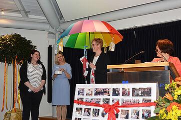 Ein Geschenk mit hoher Symbolkraft: Die Mitarbeiter versprechen, ihre neue Chefin nie im Regen stehen zu lassen.