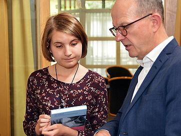 Dr. Stefan Arend gratuliert Preisträgerin Franziska Bischoff zu ihrem Beitrag.