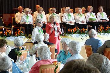 Stiftsdirektorin Monika Belowski (rotes Kleid) mit Fotografin Adelheit Mayer; auf der Bühne: Hauschor des KWA Stifts im Hohenzollernpark