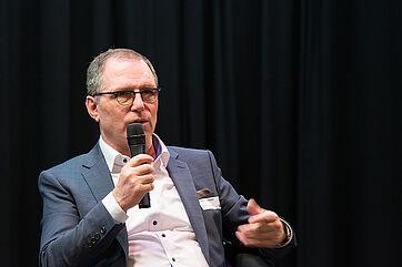 """Bernhard Schneider, als Sprecher der Initiative Pro-Pflegereform beim KWA Symposium 2020. Er sagt: """"Zur Stärkung der Kohleregionen nach dem Kohleausstieg will man 40 Mrd. Euro verteilen. Das zeigt, dass es nur eine Frage des politischen Willens ist, ob man die Pflege auch finanziell stärken will."""""""
